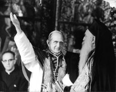 Pope Paul VI with his one hand up.