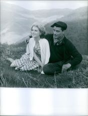 Marie-Jeanne Bardot siting with a man on the mountain, looking away and smiling. 1958