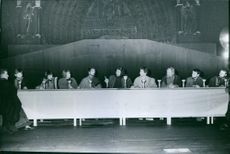 A  group of men talking and sitting in front of a long table in Notre Dame, 1962.