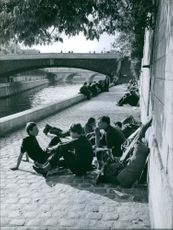 People relaxing beside river.