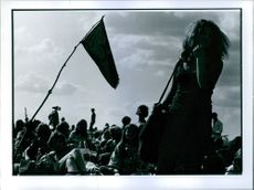 People gathered together, holding flag.