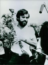 Bulgarian mountaineer, Christo Prodanov holding flowers. 1981.