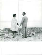 Old couple holding hands while looking at each other on the sea shore.  Taken - Circa 1965