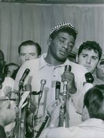 American professional boxer, Floyd Patterson speaking on the microphone. 1965.