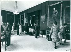 Visitors inspect painting at Art gallery of Goodwood House