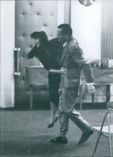 Eddie Constantine lifting woman in film scene.