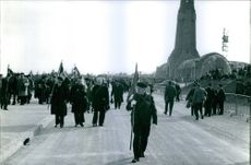 A parade of officers holding flag. 1964