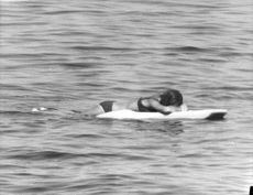 Princess Irene lying on floating board at the beach.
