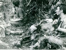 Men resting on the ground, some are smoking cigarettes in Indokina.