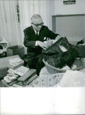 Georges Bidault packing his books in bag.