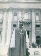 "A man standing in front of a building, facing the camera and smiling.  ""Bishop Zoa Cameroon"""