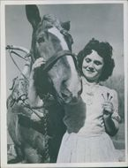 Lucienne David holding nails, while striking a pose with the horse.