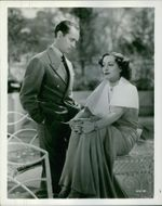 Joan Crawford sitting, man standing beside trying to talk to her.