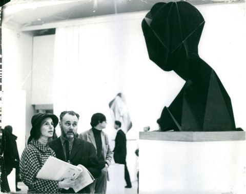 Kurt Bergengren talking to a woman while looking at a statue in a museum.