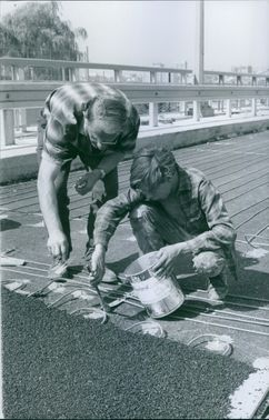 1967  Worker putting adhesives on the road for construction.