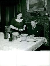 Rene Coty wife serving him a meal.