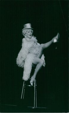Zazie Varnel on her costume sitting and performing on a high chair, 1969.