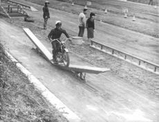 A motorcyclist riding on the long wooden plank breaking it up in half, 1961.