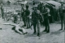 A dead soldier lying on the ground, other soldiers standing around looking and communicating.