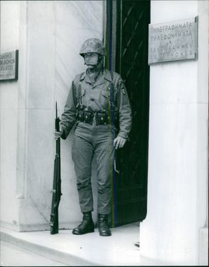 A military standing on the front door. March 8, 1957