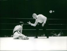 A referee counting to a knocked down boxer in a boxing ring during the Roger Menetrey and Robert Gallois fight.