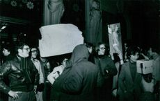 People protesting in night, holding placard.