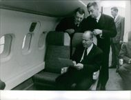 Three men inspecting a piece of paper inside the airplane.