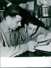 Vladimir Komarov showing a book to a boy.