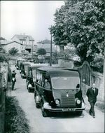 Vehicles lined up, men beside.