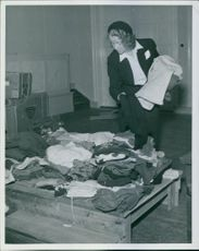 Mrs. Anna Berlin sorting clothes for refugees in 1944.
