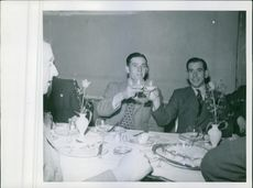 Two men toasting glass.   1939