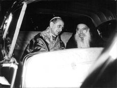 Pope Paul VI sitting in vehicle with unknown man.