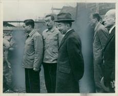 Emperor Hirohito greets the factory buildings in Yokohama, here with some workers guiding him