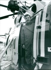 Man in overall suit standing at the entrance of an air vehicle.