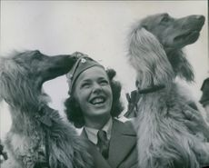 A happy girl holding her two pet dogs, 1946.