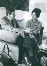 Man and woman from The Lao Royal Family siting together and talking.