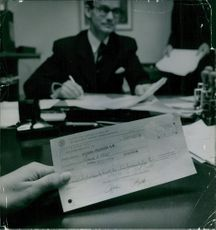 Man holding a cheque, while another man siting and writing, 1957.