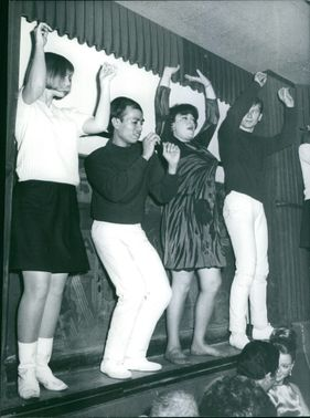 Four people, men and women standing and dancing on a side panel.