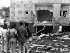 Police officers looking at destroyed building in Israel.