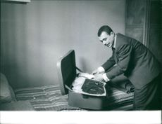 Saadi Yacef packing his things in a luggage.  Taken 24 Apr. 1962