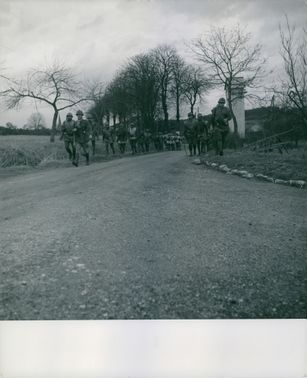 French soldiers marching on dirt road.