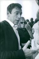 Yves Montand talking to his fans around him.