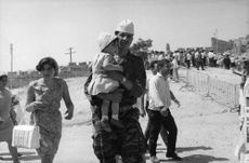 A soldier walking on the road while carrying her baby in Israel.