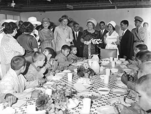 Queen Juliana in a public gathering, beside the dining table where children are dining.