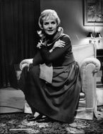 Carroll Baker sitting on sofa.