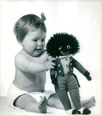 A baby wearing a ribbon on her hair is cheerfully playing with her toy.