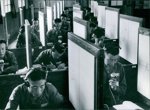 Officers sitting on their respective cubicles wearing headphones.