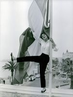 Italian actress Rossana Podestà posing with 1 foot up and holding on a pole with the flag of Italy, 1961.