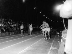 Two athletes running during race as the others looking at them.
