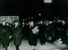 People gathered and few men waving towards crowd in night.